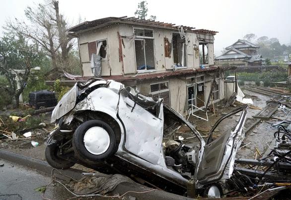 Nhà cửa bị xé toạc trong khi xe cộ nằm nghiêng ngã ở thành phố Ichihara, tỉnh Chiba ngày 12-10 - Ảnh: AP